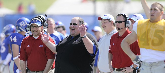 Former Kansas University head coach Mark Mangino, now the offensive coordinator at Iowa State, has a laugh on the sidelines during the second half of the 2009 Spring Game at Memorial Stadium, as current KU coach David Beaty (in red, at right), then the Jayhawks' wide receivers coach, stands nearby.