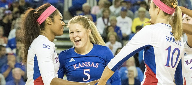 Kansas' Tiana Dockery, left, Cassie Wait (5) and Tayler Soucie (10) celebrate a kill by Dockery during the Jayhawks' volleyball match against West Virgina Saturday afternoon at the Horejsi Center. The Jayhawks won, 3-0, and improved to 15-0 on the year.