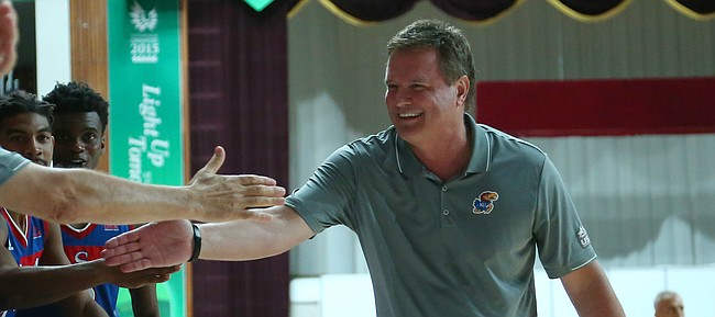 Team USA coach Bill Self congratulates the players on the bench in the closing seconds of the United States' 78-68 semifinal victory over Russia on Sunday, July 12, 2015, at the World University Games in South Korea.