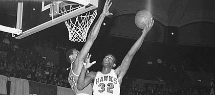 Wilt Chamberlain of the Philadelphia 76ers reaches to block the shot of Bill Bridges (32) of the St. Louis Hawks in National Basketball Assn., game in St. Louis, on Sunday, afternoon, Jan. 29, 1967.