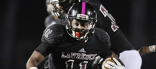 Lawrence senior JD Woods heads into the end zone for his fourth first-half touchdown in a 63-7 victory over Olathe South on Friday, Oct. 9, 2015, at LHS.
