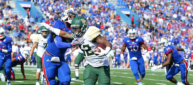 Baylor running back Shock Linwood (32) pushes aside Kansas linebacker Marcquis Roberts (5) on a run during the first quarter on Saturday, Oct. 10, 2015 at Memorial Stadium.
