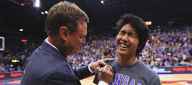 Kansas head coach Bill Self writes out a check to Jerrod Martin Castro, Topeka sophomore, after director of basketball operations Brennan Bechard hit a half-court shot which awarded Castro the personal check from Self during Late Night in the Phog, Friday, Oct. 9, 2015 at Allen Fieldhouse.