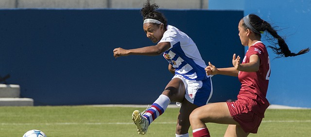 Kansas senior forward Ashley Williams gets a shot on goal off past Oklahoma freshman defender Paige Welch during their soccer match Sunday at Rock Chalk Park.