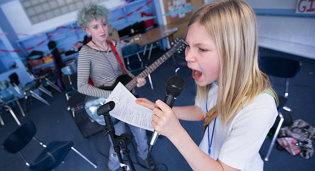 Vocalist Ada Hyde, 11, belts out the lyrics to the Girls Rock Anthem as Macie Orr, 13, plays guitar during the Girls Rock Lawrence camp, Tuesday, June 2, 2015 at Saint John's Catholic School. Both girls are performing with the band Candle Stick during the weeklong camp, which seeks to empower girls through musical collaboration and performance. The camp also aims among other things, to expunge the stigma that girls are weak. To view a video from the camp, please visit ljworld.com/girlsrock2015
