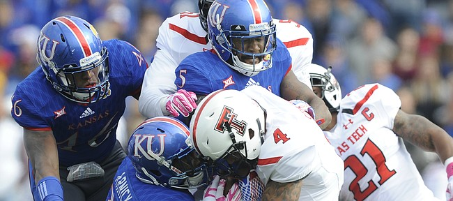 Kansas linebackers Courtney Arnick (28) and Marcquis Roberts (5), and defensive end Dorance Armstrong Jr. (46) work to bring down Texas Tech running back Justin Stockton (4) during the first quarter on Saturday, Oct. 17, 2015 at Memorial Stadium.