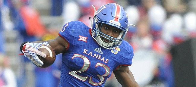 Kansas running back De'Andre Mann (23) escapes a tackle by Texas Tech defensive back Jah'Shawn Johnson (7) during the first quarter on Saturday, Oct. 17, 2015 at Memorial Stadium.