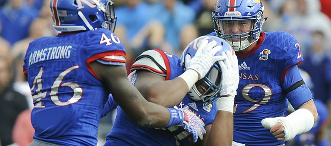Kansas defensive tackle Daniel Wise (96) reacts after narrowly missing an interception during the first quarter on Saturday, Oct. 17, 2015 at Memorial Stadium. Also pictured are Kansas defensive end Dorance Armstrong Jr. (46) and linebacker Joe Dineen Jr. (29).