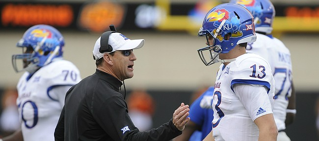 Kansas head coach David Beaty gives quarterback Ryan Willis a pat after a three and out during the second quarter on Saturday, Oct. 24, 2015 at T. Boone Pickens Stadium in Stillwater, Okla.