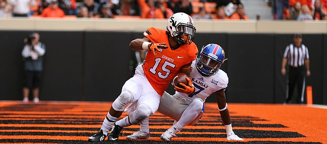 Oklahoma State wide receiver Chris Lacy (15) rolls onto his feet after a touchdown while covered by Kansas cornerback Derrick Neal (7) during the third quarter on Saturday, Oct. 24, 2015 at T. Boone Pickens Stadium in Stillwater, Okla.