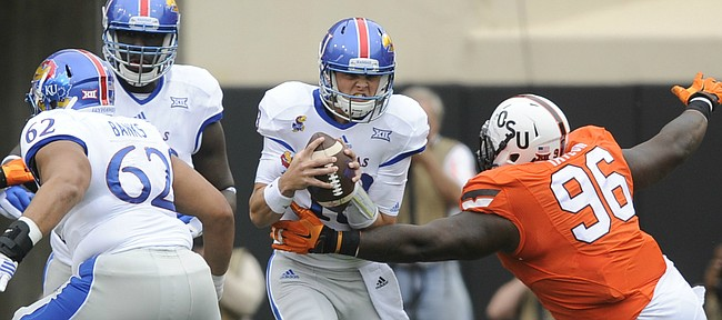 Kansas quarterback Ryan Willis (13) is wrapped up for a sack by Oklahoma State defensive tackle Vincent Taylor (96) during the first quarter on Saturday, Oct. 24, 2015 at T. Boone Pickens Stadium in Stillwater, Okla.