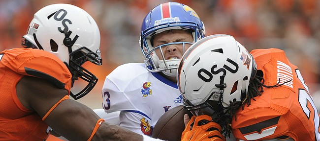 Kansas quarterback Ryan Willis (13) is sacked by several Oklahoma State defenders including Oklahoma State linebacker Jordan Burton (20) and defensive end Emmanuel Ogbah (38) during the first quarter on Saturday, Oct. 24, 2015 at T. Boone Pickens Stadium in Stillwater, Okla.