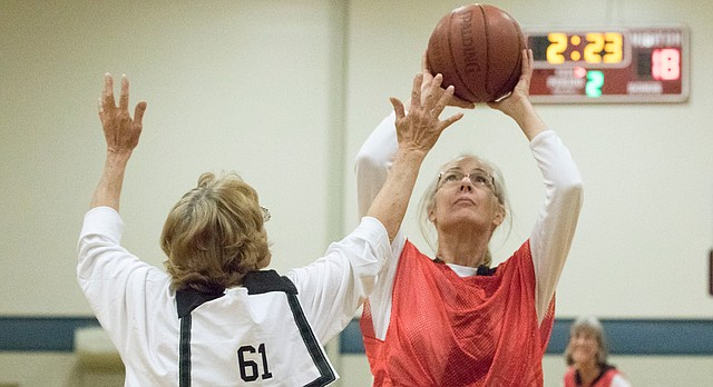 Michele Clark, of Berryton, puts up a shot over Llynde Lacey (61), of Lawrence, as the two scrimmage during the first game of the Granny Basketball League in Kansas on Saturday evening, Oct. 24, 2015, at Holcom Park Recreational Center, 2700 W. 27th St.