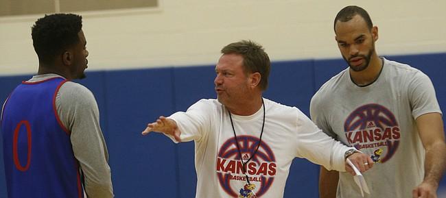 Kansas coach Bill Self, center, runs through a play with Jamari Traylor, left, and Perry Ellis.