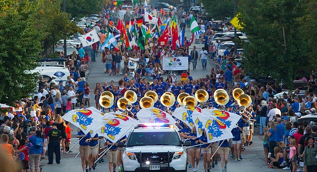 Spectators line the streets as the 2014 KU homecoming parade marches north on Massachusetts Street on Friday, Sept. 26, 2014, in downtown Lawrence.