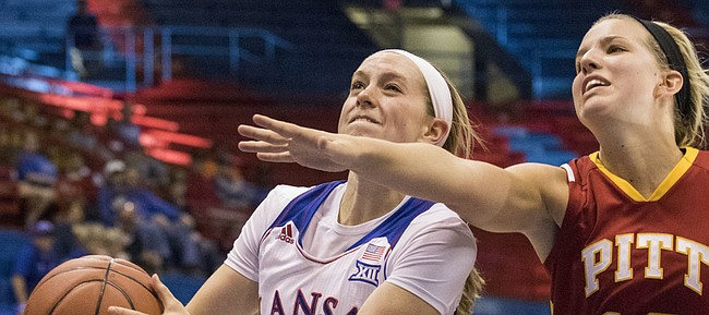 Kansas sophomore Lauren Aldridge, left, makes a move to the basket past the outstretched arm of Pittsburg State junior Paige Lungwitz (10)  during their exhibition game Sunday afternoon in Allen Fieldhouse. Although the Jayhawks got off to a slow start and only led by four at halftime, they pulled away in the second half for a 80-54 victory over the Gorillas.