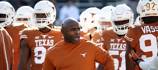 In this Oct. 10, 2015, Texas head coach Charlie Strong talks with his team during warm-ups before an NCAA college football game against Oklahoma in Dallas.