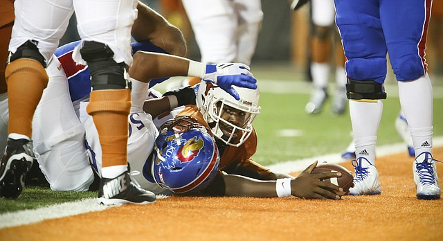 Texas quarterback Tyrone Swoopes (18) squeezes in for a touchdown past Kansas defensive end Anthony Olobia (56) during the first quarter on Saturday, Nov. 7, 2015 at Darrell K. Royal Stadium in Austin, Texas.