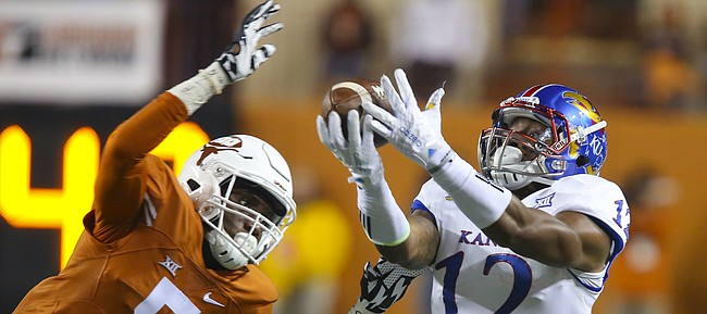 Kansas wide receiver Darious Crawley (12) eyes the ball as Texas defensive back Holton Hill (5) swoops in to bat it away during the third quarter on Saturday, Nov. 7, 2015 at Darrell K. Royal Stadium in Austin, Texas.