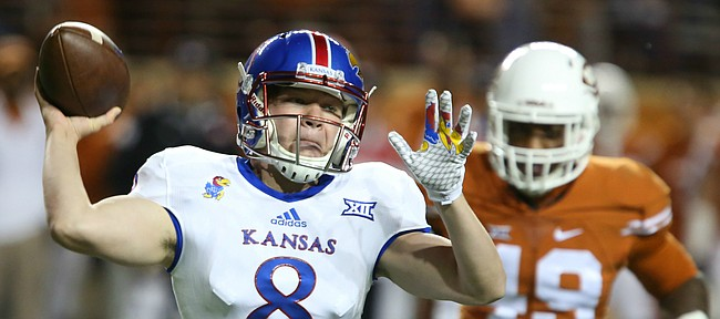 Kansas backup quarterback Keaton Perry (8) pulls back to throws as Texas safety Kevin Vaccaro (18) closes in during the fourth quarter on Saturday, Nov. 7, 2015 at Darrell K. Royal Stadium in Austin, Texas.