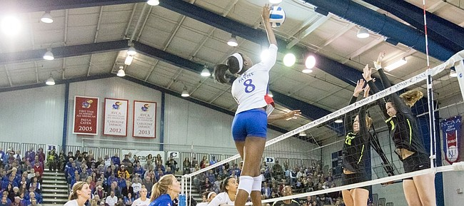 Kansas sophomore Kelsie Payne (8) goes up to spike the ball while being challenged by Baylor's Adrien Richburg (20) and Andie Malloy (8)  their volleyball match Saturday afternoon at the Horejsi Center.