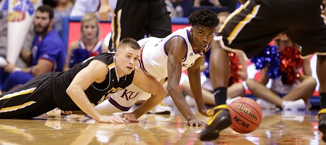 Kansas guard Lagerald Vick (2) and Fort Hays State forward Dom Samac (24) slides across the floor while competing for a loose ball during the first half, Tuesday, Nov. 10, 2015 at Allen Fieldhouse.