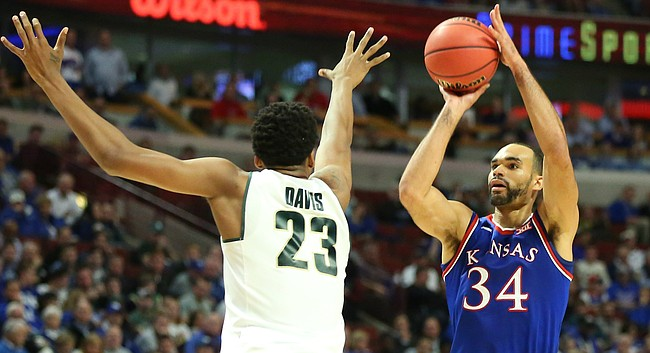 Kansas forward Perry Ellis (34) pulls up for a three against Michigan State forward Deyonta Davis (23) during the first half, Tuesday, Nov. 17, 2015 at United Center in Chicago.