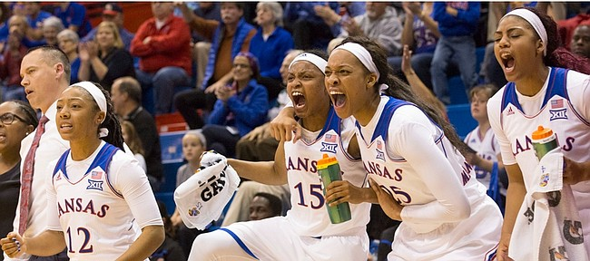 From left, Kansas' Timeka O'Neal (12), Aisia Robertson (15), Caelynn Manning-Allen (25) and Jada Brown cheer from the bench during their game against Memphis Thursday, Nov. 19, 2015, at Allen Fieldhouse.