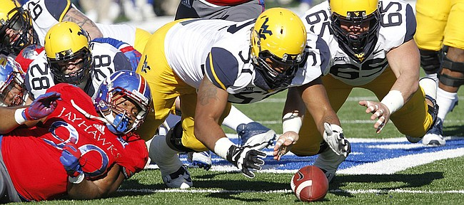 Kansas defensive tackle Kapil Fletcher, left, (90) watches as West Virginia offensive lineman recover a WV fumble early in the first-half against the West Virginia Mountaineers Saturday, Nov. 21, 2015, at Memorial Stadium.