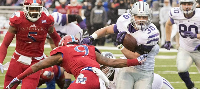 Kansas State fullback Winston Dimel (38) runs through an arm tackle by Kansas junior safety Fish Smithson (9) during the annual Sunflower Showdown game Saturday at Memorial Stadium.