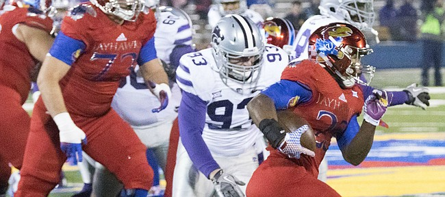 Kansas senior running back De'Andre Mann (23) tries to take the ball outside as he is pursued by Kansas State sophomore defensive end Davis Clark (93) during the Sunflower Showdown game Saturday at Memorial Stadium.