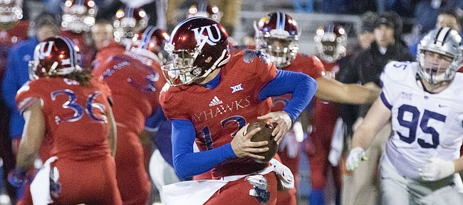 Kansas freshman quarterback Ryan Willis pulls the ball down to run after being flushed out of the pocket by the Kansas State defense during the Sunflower Showdown game Saturday at Memorial Stadium.