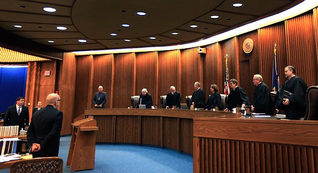 Justices take their seats to hear oral arguments in a judicial funding case before the Kansas Supreme Court in Topeka, Kan., Thursday, Dec. 10, 2015.