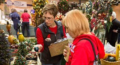 Lawrence residents Gayle Stuber, left, and Lynn Heffley look through holiday decor for sale at the annual Holiday Farmer's Market Saturday, Dec. 13, 2014, at the Holiday Inn Convention Center, 200 McDonald Drive.