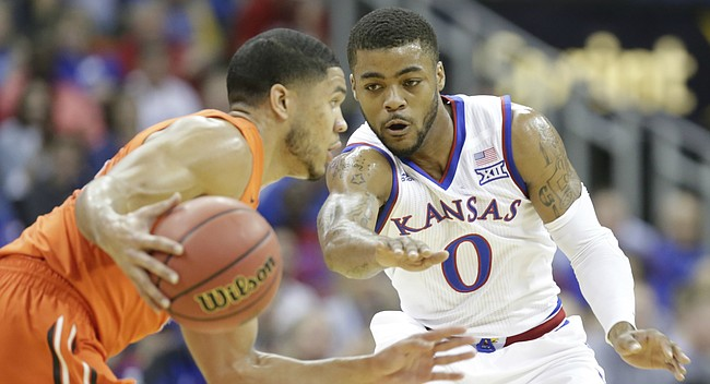 Kansas guard Frank Mason III (0) defends against a drive by Oregon State guard Malcolm Duvivier (11) during the first half, Saturday, Dec. 12, 2015 at Sprint Center.