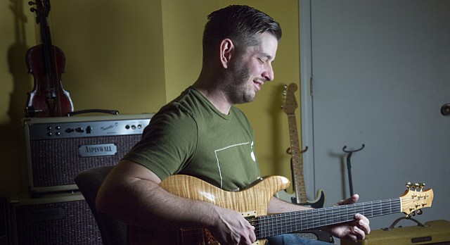 Guitar maker Danny Corwin, of Lawrence and owner of Corwin Guitar Co., plays a guitar he made about 13 years ago. Some local musicians have sought ought Corwin and his business to craft specialized guitars.