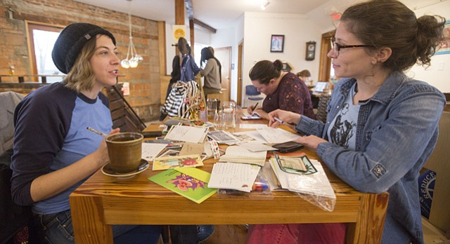 Carly Efros, left, and Katy Willson, both of Lawrence, chat over letters and stationery during a meeting of the Wonder Fair Letter Writing Club at Decade coffee shop, 920 Delaware Street on Sunday, Dec. 13, 2015.