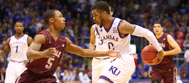 Kansas guard Frank Mason III (0) goes behind the back to get around Montana guard Walter Wright (5) for a bucket during the first half, Saturday, Dec. 19, 2015 at Allen Fieldhouse.