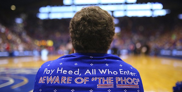 """A familiar phrase is stitched on the back of a Kansas University """"ugly"""" Christmas sweater as a member of the cheer squad takes a seat on the sideline during the second half, Saturday, Dec. 19, 2015 at Allen Fieldhouse."""