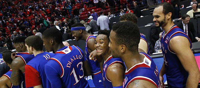Kansas guard Devonte' Graham flashes a wide smile as he and the Jayhawks wait to slap hands with San Diego State players after their 70-57 win, Tuesday, Dec. 22, 2015 at Viejas Arena in San Diego.