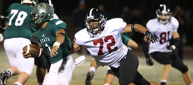 Lawrence High defensive lineman Amani Bledsoe (72) comes around to wrap up Free State quarterback Bryce Torneden (1) for a sack during the first half on Friday, Sept. 17, 2015 at Free State High School.