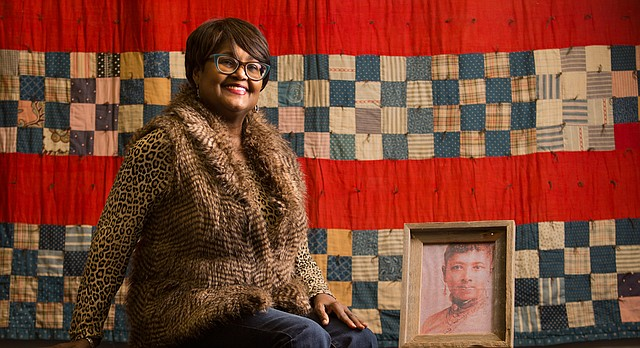 Lawrence quilt artist Marla Jackson is pictured before an 1890s quilt from an unknown artist at the African American Quilt Museum and Textile Academy, 2001 Haskell Ave. Jackson recently received a grant from the Kansas Creative Arts Industries Commission to renovate the museum space. Next to Jackson on the bench is a framed portrait of Maria Rodgers Martin, who was born a slave in 1831. Quilts made by Martin will be rotated through the museum.