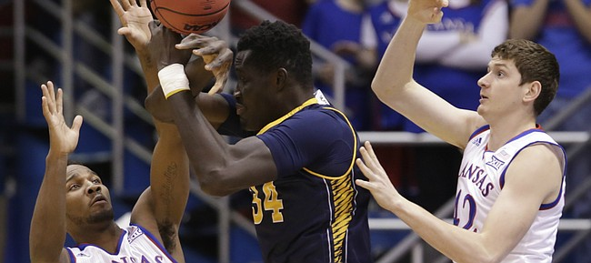 Kansas guard Wayne Selden Jr. (1) and forward Hunter Mickelson (42) knock the ball loose from the grip of UC Irvine center Mamadou Ndiaye (34) during the first half, Tuesday, Dec. 29, 2015 at Allen Fieldhouse.
