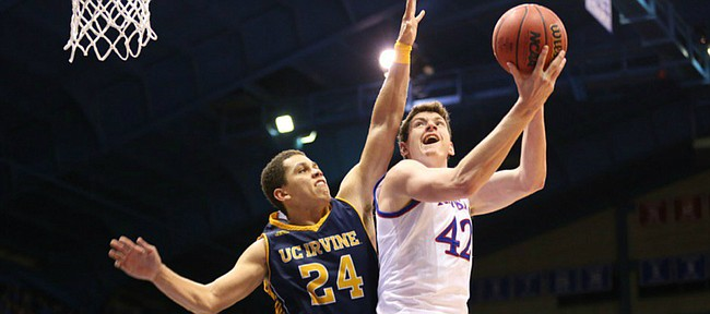 Kansas forward Hunter Mickelson (42) looks to the bucket for a shot as he is fouled by UC Irvine guard Dominique Dunning (24) during the second half, Tuesday, Dec. 29, 2015 at Allen Fieldhouse.