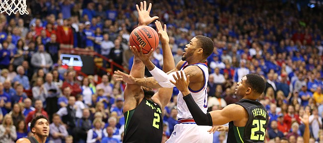 Kansas guard Frank Mason III (0) hangs for a shot in the lane against Baylor forward Rico Gathers (2) and guard Al Freeman (25) during the first half, Saturday, Jan. 2, 2016 at Allen Fieldhouse.