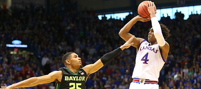 Kansas guard Devonte' Graham (4) pulls up for a three against Baylor guard Al Freeman (25) during the first half, Saturday, Jan. 2, 2016 at Allen Fieldhouse. At left is Kansas forward Cheick Diallo (13).