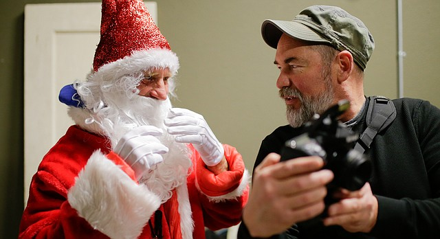 Dennis Abbott and John Clayton converse while reviewing shots at their annual Santa Claus photo shoot. Clayton is the photographer behind the popular The Friends of Dennis Facebook page, which documents Abbotts' zany outfits and everyday interactions.