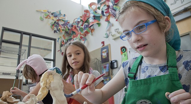 """Julia Rathmel, 8, paints a sculpted figurine during a """"Raiders of the Lost Art"""" ArtSpace summer camp at the Lawrence Arts Center on July 18, 2014."""