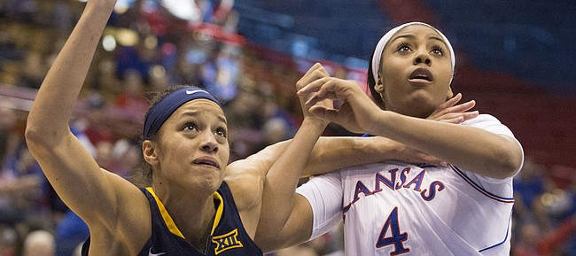 West Virginia forward Arielle Roberson (32) and Kansas junior forward Jada Brown (4) fight for rebounding position during their game Sunday afternoon at Allen Fieldhouse. The Jayhawks dropped their fourth straight game, losing to the Mountaineers, 65-45.