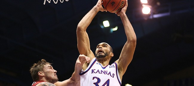 Kansas forward Perry Ellis (34) gets fouled by Oklahoma forward Ryan Spangler (00) on his way to the bucket during the second half, Monday, Jan. 4, 2016 at Allen Fieldhouse.